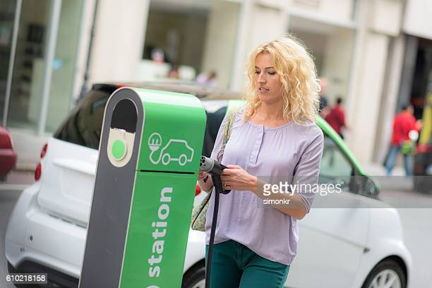 Woman holding a plug by the charging station
