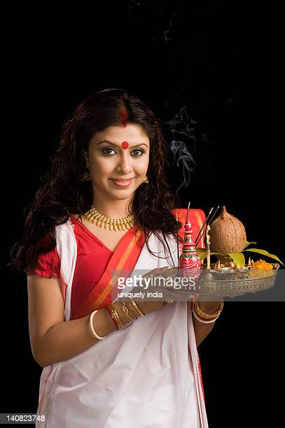 Woman holding a puja thali at Durga puja