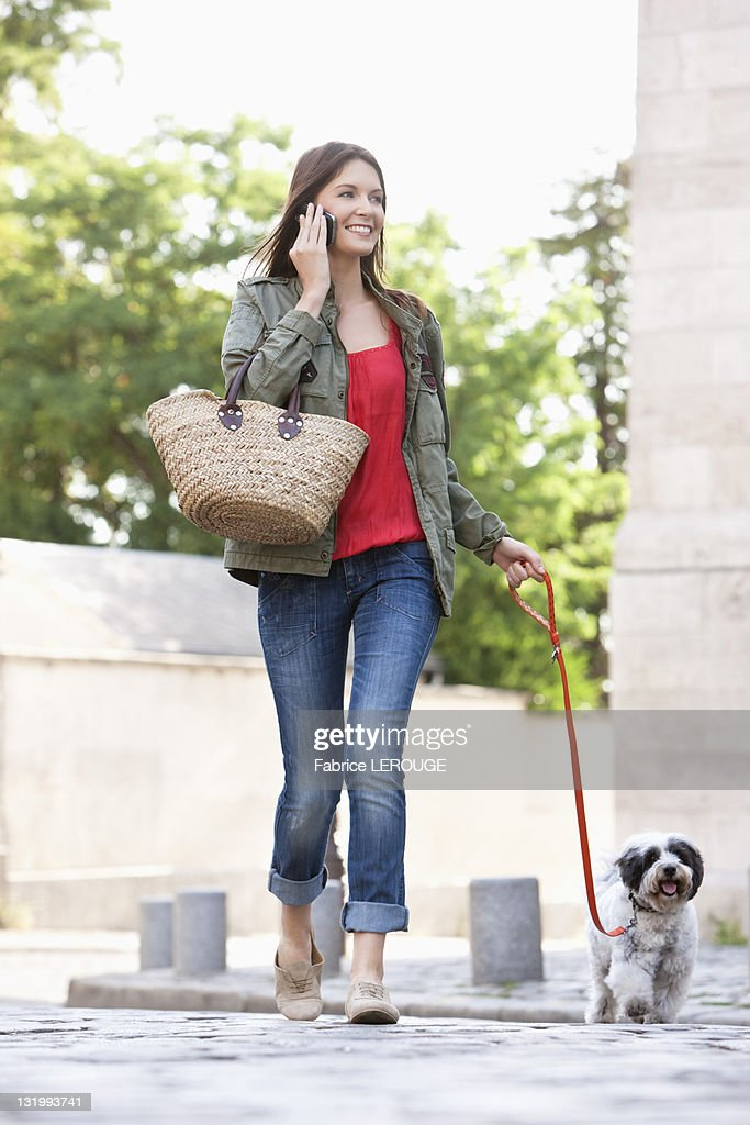 Woman holding a puppy on leash while talking on a mobile phone, Paris, Ile-de-France, France : Stock Photo