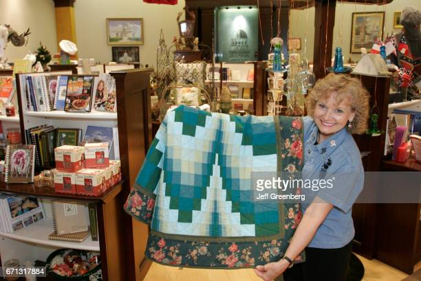 A woman holding a quilt in the Goat Hill Museum Store