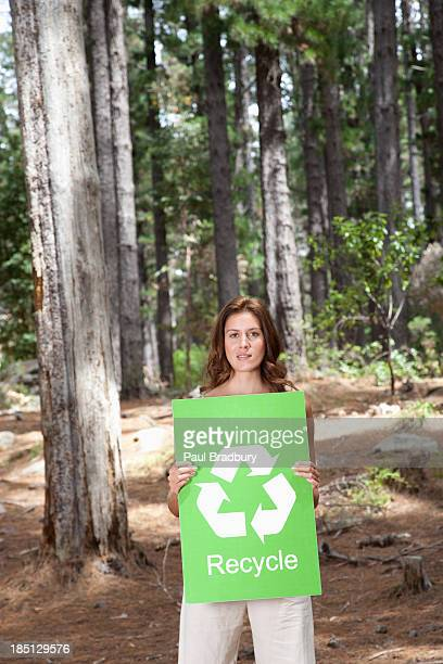 A woman holding a recycling sign