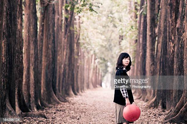 Woman holding a red lantern in the forest