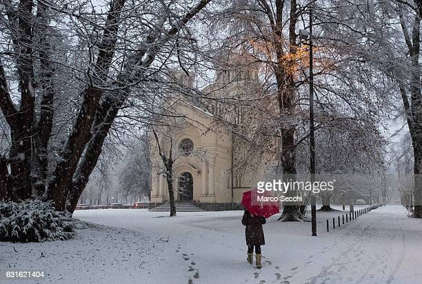 A woman holding a red umbrella walks towards the Orthodox church on January 13 2017 in Ljubljana Slovenia Most of Slovenia was covered by heavy...