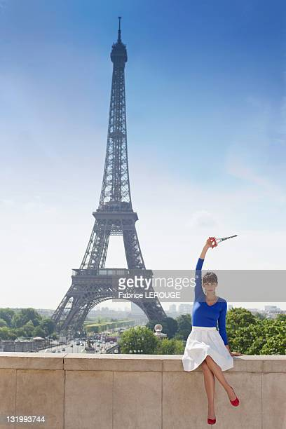 Woman holding a replica of Eiffel Tower sitting on a stone wall with the Eiffel Tower in the background, Paris, Ile-de-France, France