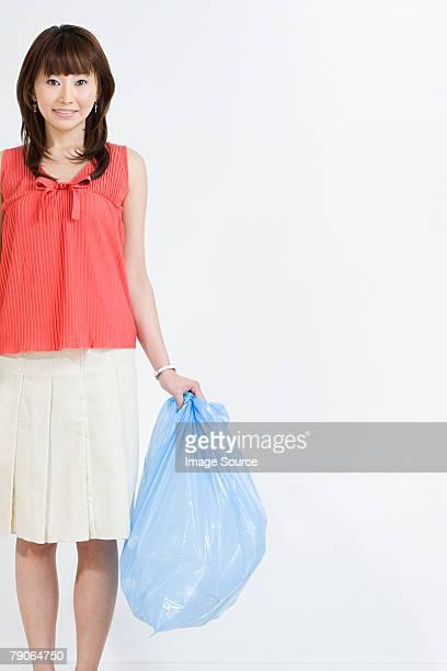 Eine Frau hält eine Tasche Müll