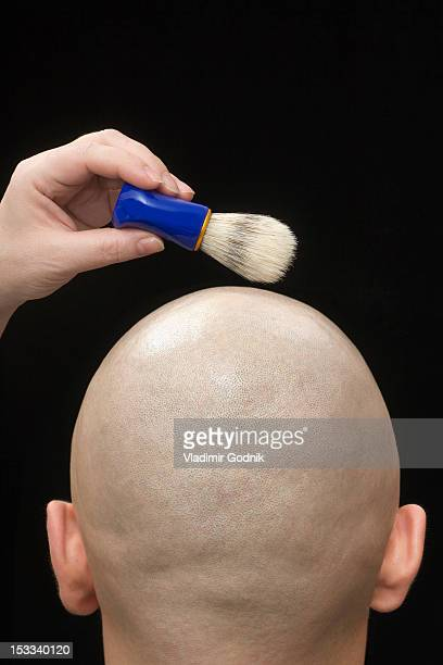 A woman holding a shaving brush above the shaved head of a man