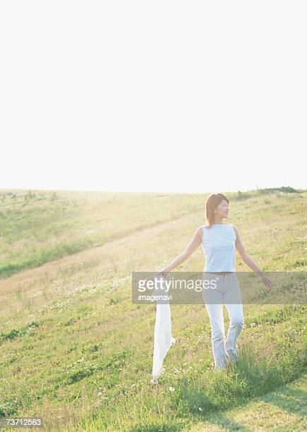 Woman holding a shirt in field