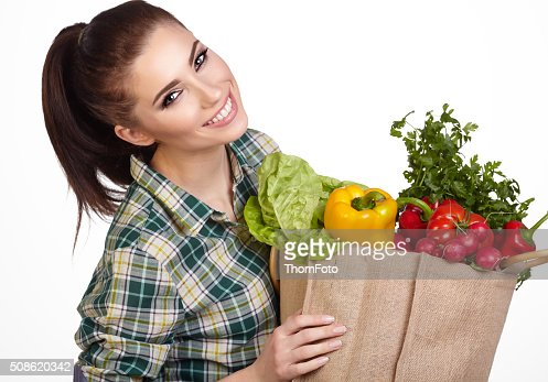 Woman holding a shopping bag full of fresh food : Stock Photo