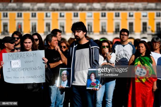 A woman holding a sign reading '109 people died because of your incompetence What weight in consciousness' stands next to a man holding the portraits...