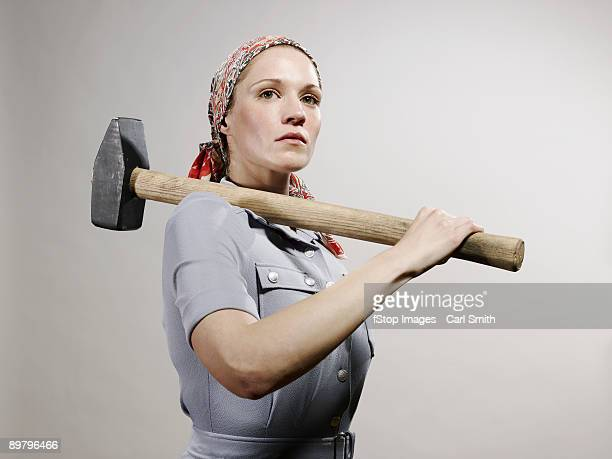 A woman holding a sledgehammer over her shoulder