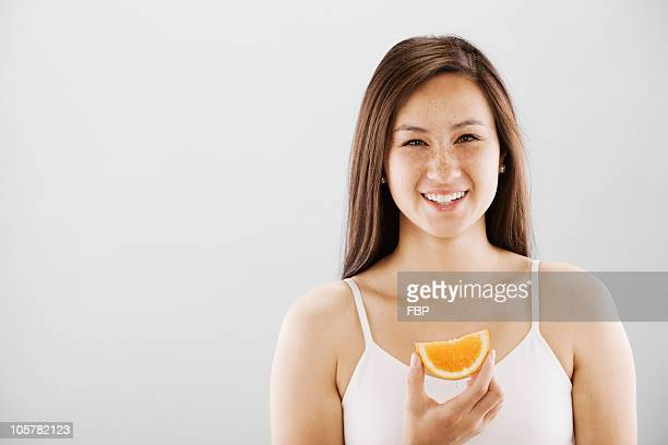 Woman holding a slice of orange