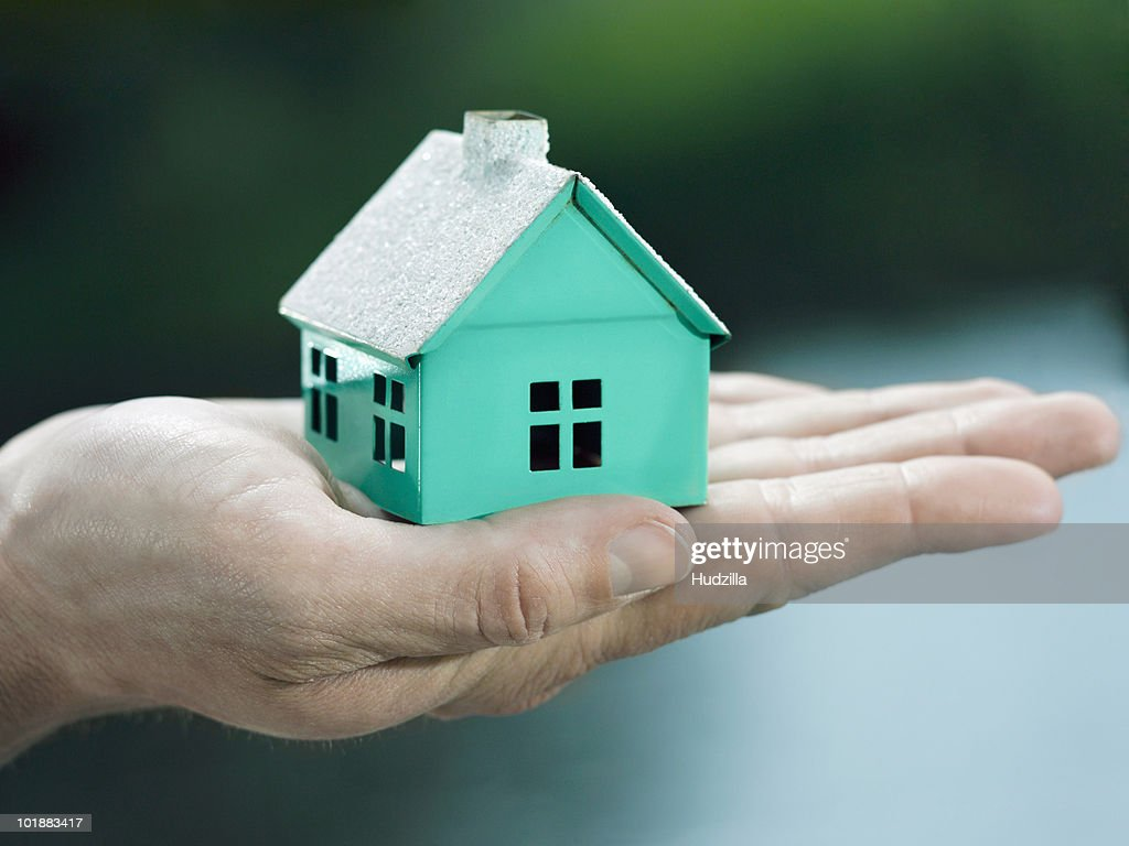 A woman holding a small house on her palm, focus on the hand : Photo