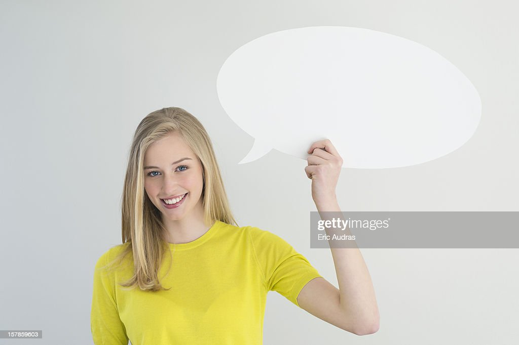 Woman holding a speech bubble and smiling