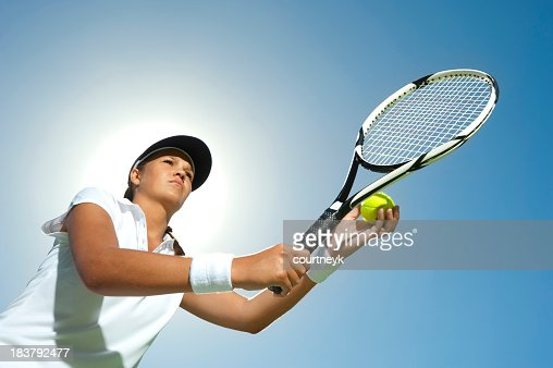 Woman holding a tennis racquet ready to serve