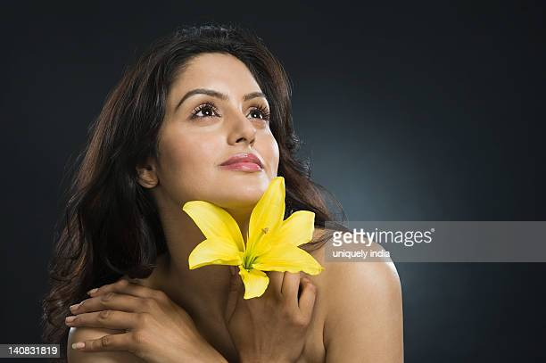 Woman holding a Tiger Lily flower and day dreaming