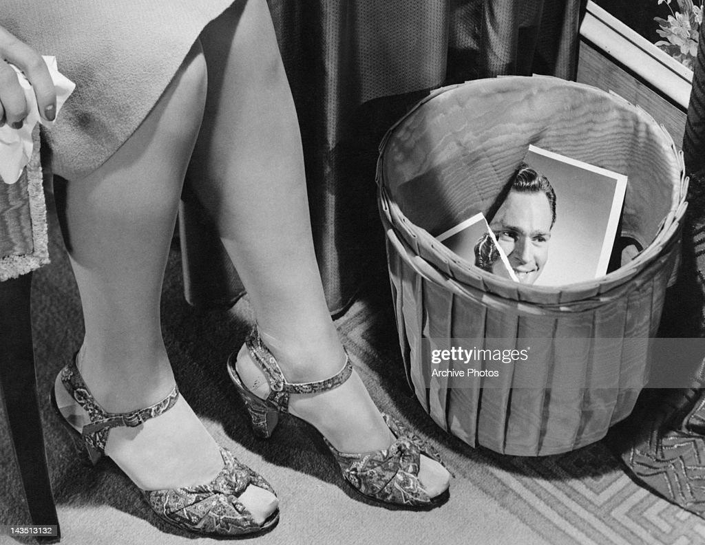 A woman holding a tissue as she sits by a wastepaper basket containing the torn photograph of a man, circa 1955.