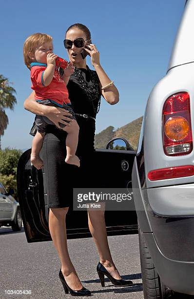 A woman holding a toddler and using a mobile phone while standing next to a car