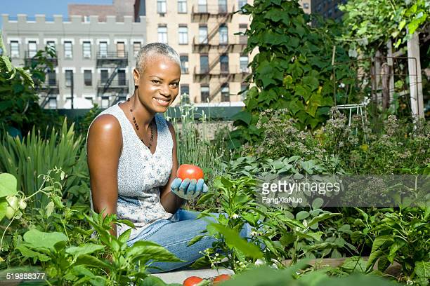 Woman holding a tomato in a community garden