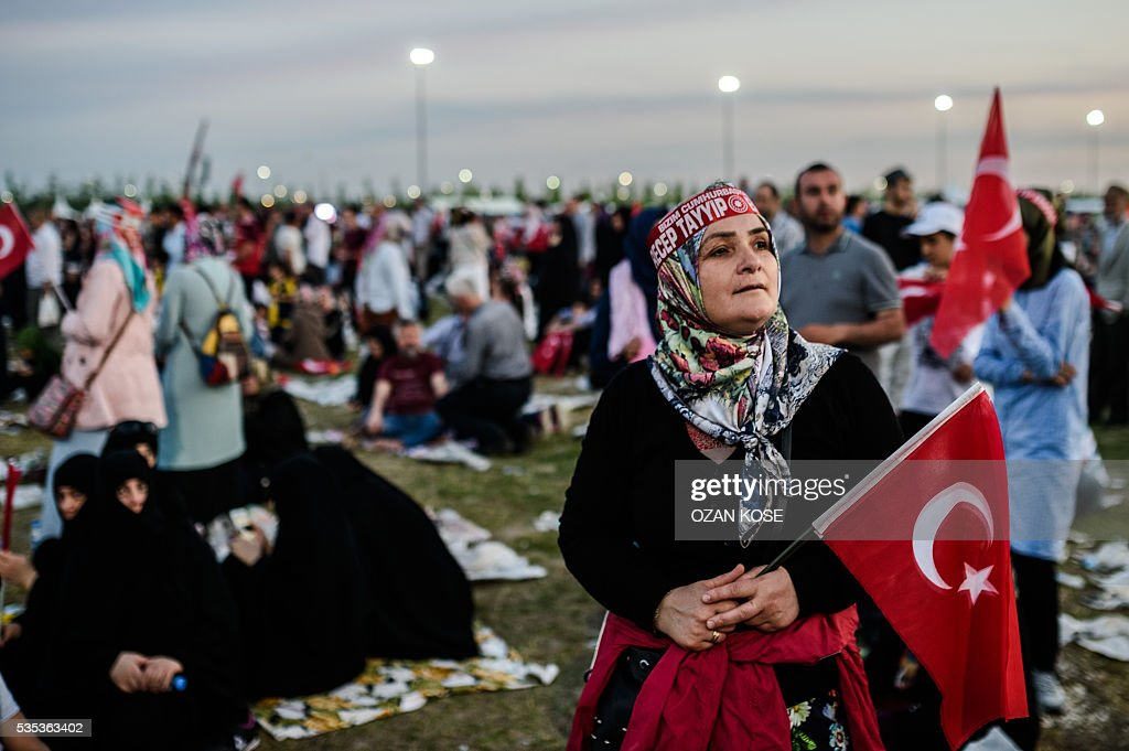 A woman holding a Turkish national flag listens at Turkish President during a rally to mark the 563rd anniversary of the conquest of Istanbul by Ottoman Turks on May 29, 2016 in Istanbul. / AFP / OZAN