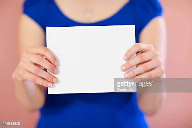 Woman holding a white card in front