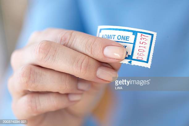 Woman holding admission ticket, close-up