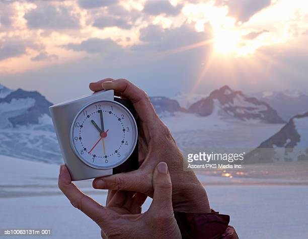Woman holding alarm clock, close-up of hands, mountain range in background