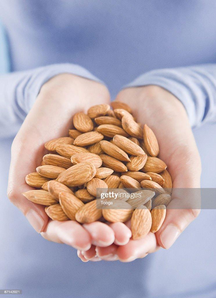Woman holding almonds : Stock Photo