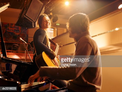 Woman Holding an Acoustic Guitar Leaning Against a Piano and Smiling at a Male Pianist