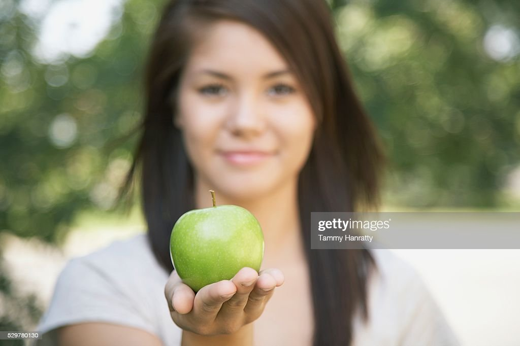 Woman holding an apple : Stock Photo