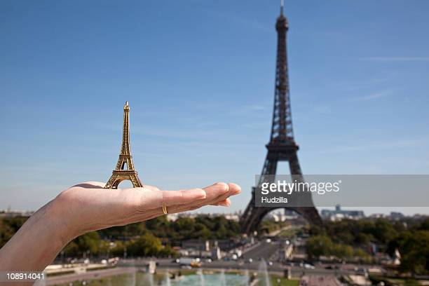 A woman holding an Eiffel Tower replica souvenir next to the real Eiffel Tower, focus on hand