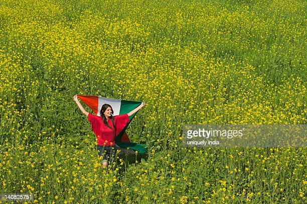 Woman holding an Indian flag and running in an oilseed rape field