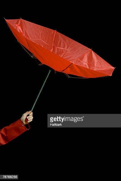 A woman holding an inside out umbrella