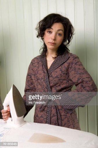 A woman holding an iron next to a burnt shirt