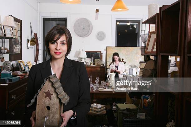 A woman holding an old birdhouse in an antiques shop