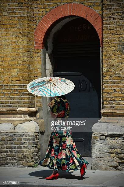 A woman holding an oldfashioned umbrella to shelter her from the sun walks along a street in central London on July 17 2014 Meteorologists expect...