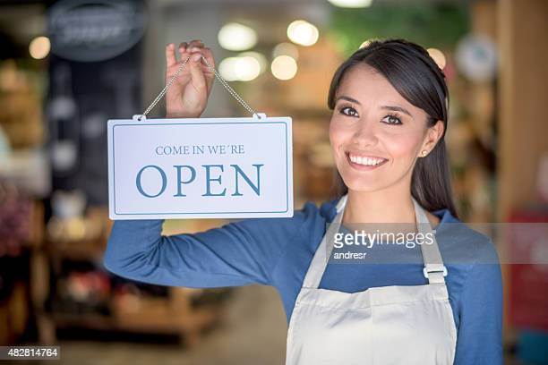 Woman holding an open sign at a grocery store