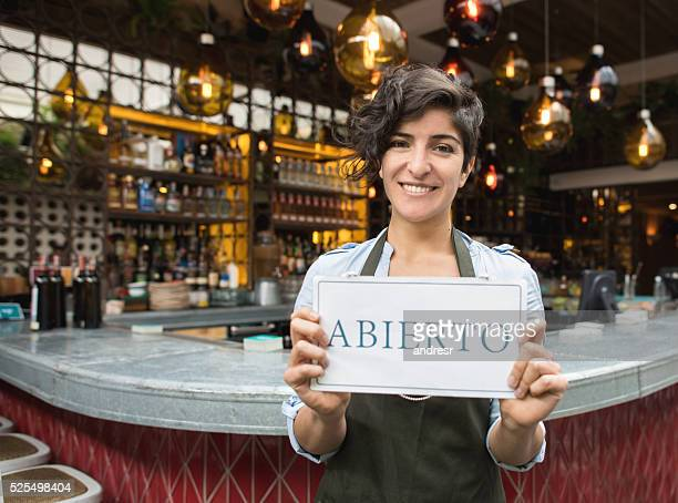 Woman holding an open sign in Spanish at a restaurant