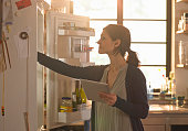Woman holding an iPad whilst looking in the fridge