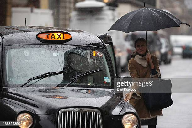 A woman holding an umbrella catches a taxi in the pouring rain on January 3 2012 in London United Kingdom Much of the UK has encountered wet and...