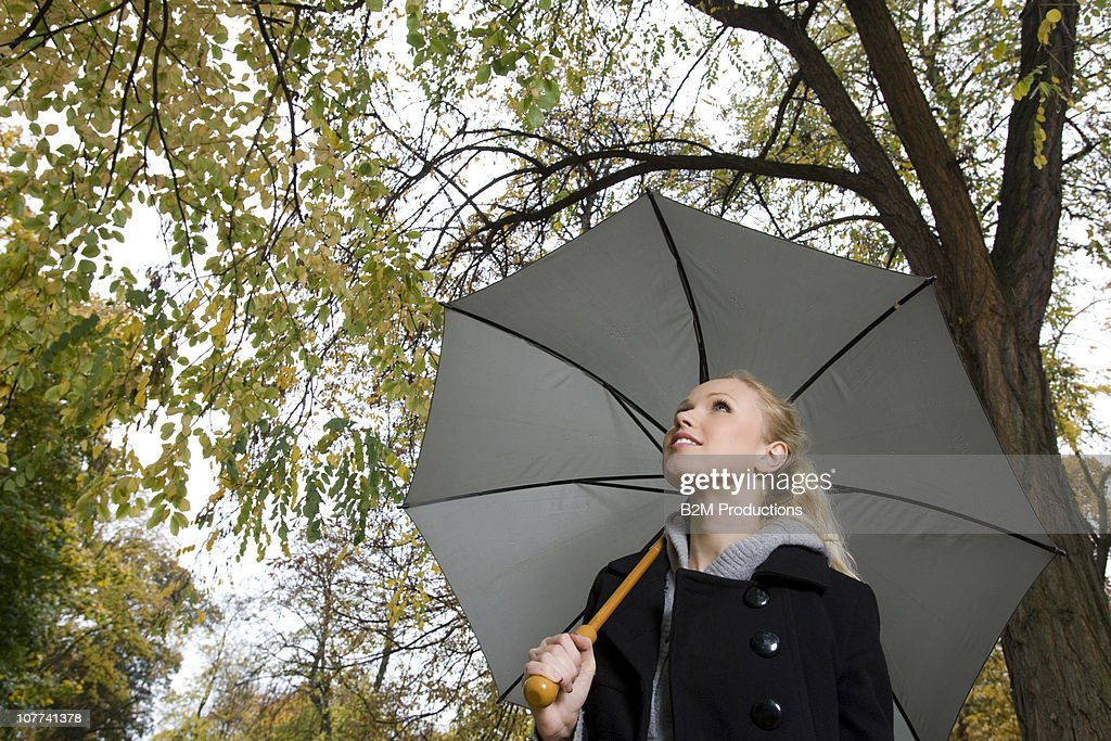 Woman holding an umbrella in a forest : Stock Photo