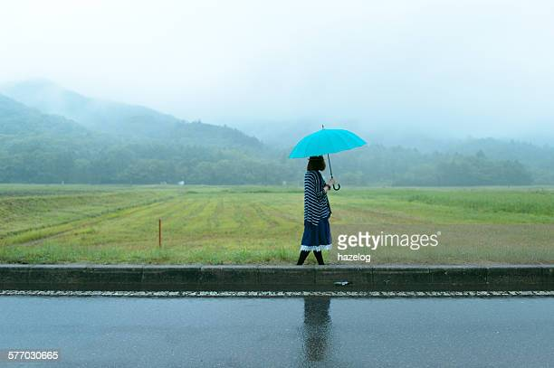 Woman holding an umbrella in a rice field