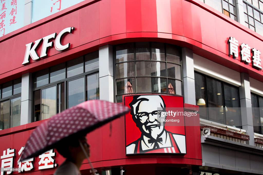 A woman holding an umbrella walks past a KFC restaurant, operated by Yum! Brands Inc., in the pedestrianized Dongmen area of Shenzhen, China, on Monday, Aug. 4, 2014. Yum, owner of KFC and Pizza Hut, said its China team is trying to regain customers after a supply chain scare has recently hurt results. Photographer: Brent Lewin/Bloomberg via Getty Images