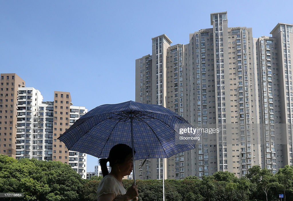 A woman holding an umbrella walks past residential buildings in Shanghai, China, on Sunday, June 30, 2013. China's President Xi Jinping said officials shouldn't be judged solely on their record in boosting gross domestic product, the latest signal that policy makers are prepared to tolerate slower economic expansion. Photographer: Tomohiro Ohsumi/Bloomberg via Getty Images