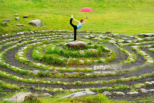 Woman holding an umbrella whilst in yoga pose in centre of stone maze