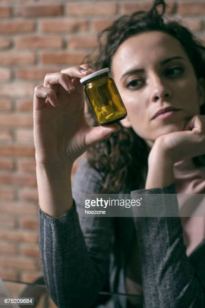 Woman holding and looking on a pill.