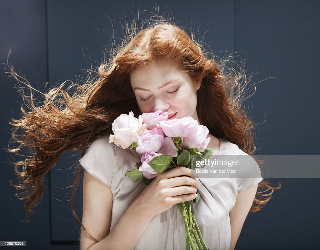 Woman holding and smelling bunch of roses : Stock Photo