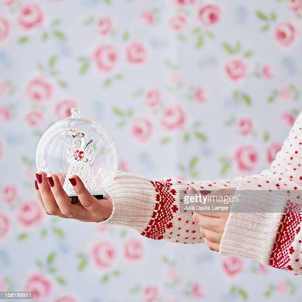 Woman holding angel globe