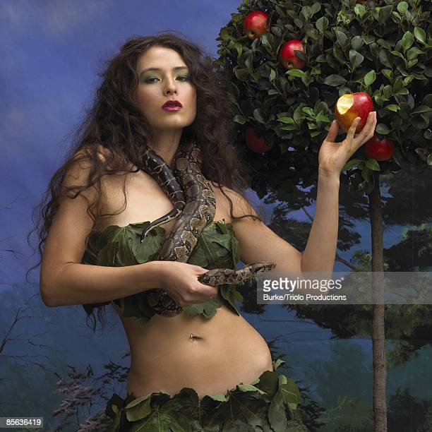 Woman holding apple and snake in garden