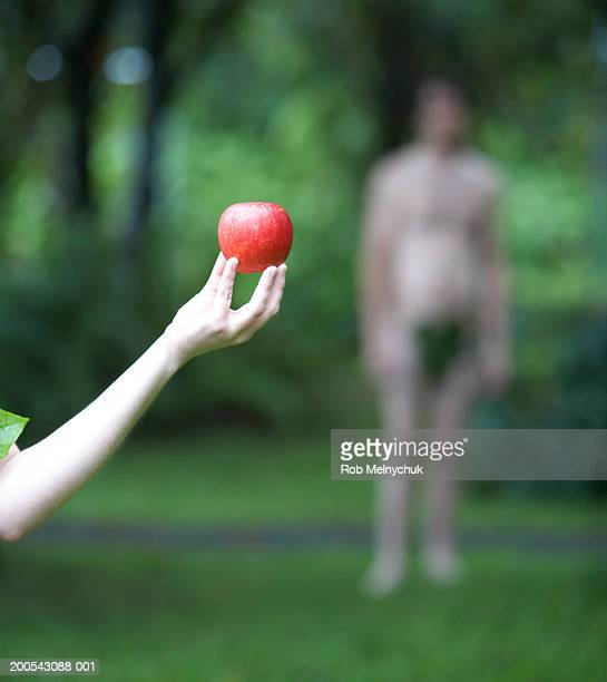 Woman holding apple in forest, man in background (focus on apple)