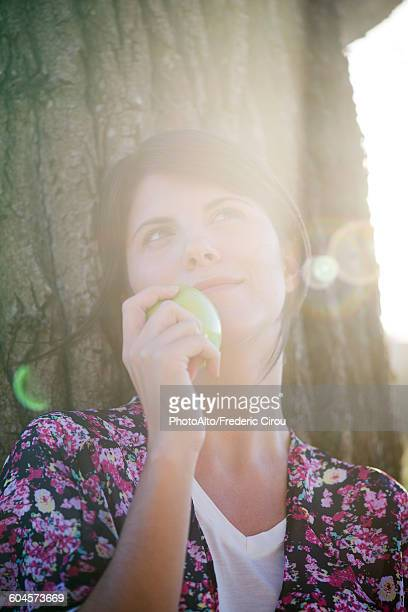 Woman holding apple, looking up dreamily, portrait